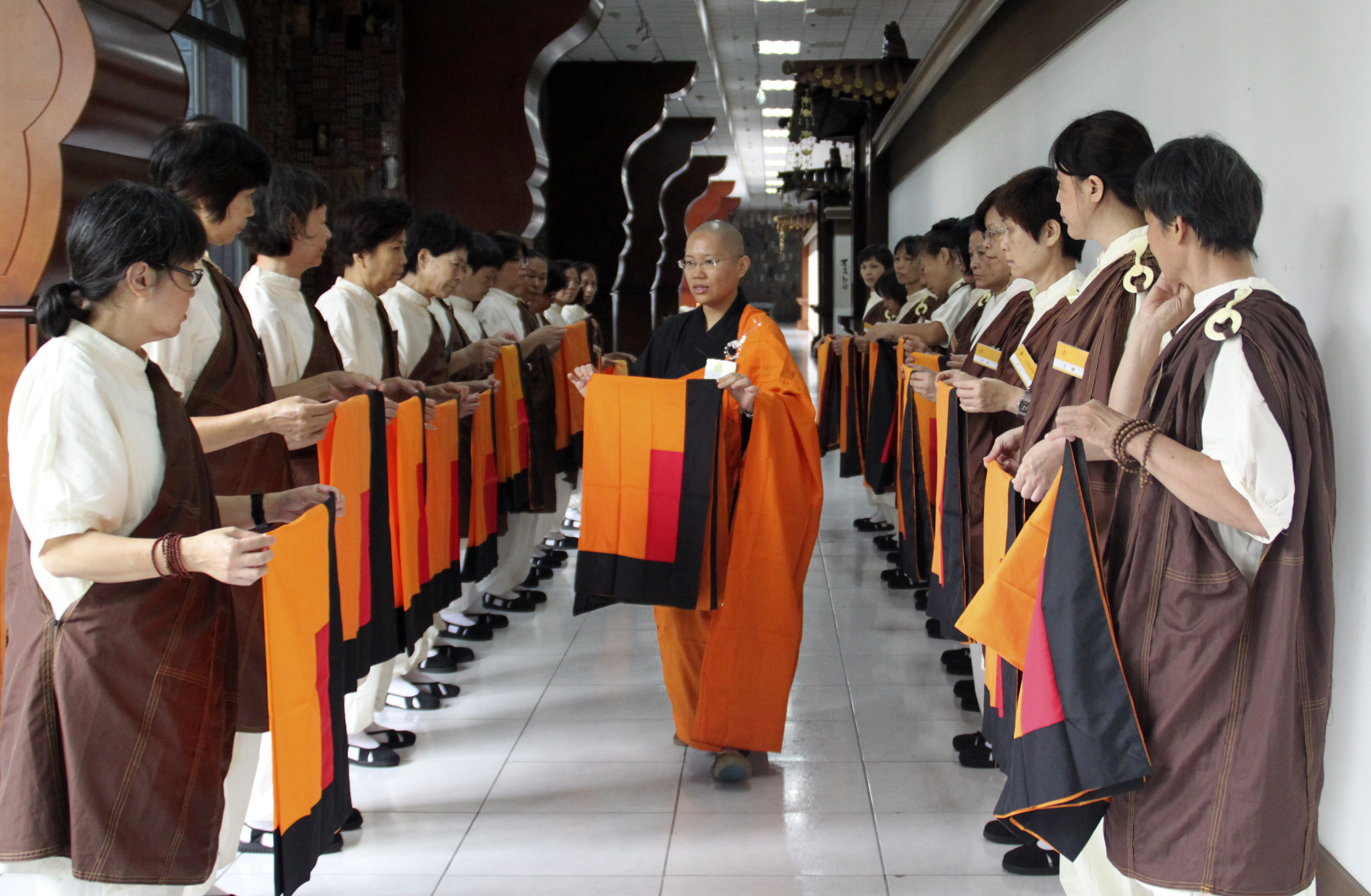 A guiding venerable shows a class of new preceptees how to fold the sitting mat, Fo Guang Shan Headquarters, 2016. Photo by Life News Agency.