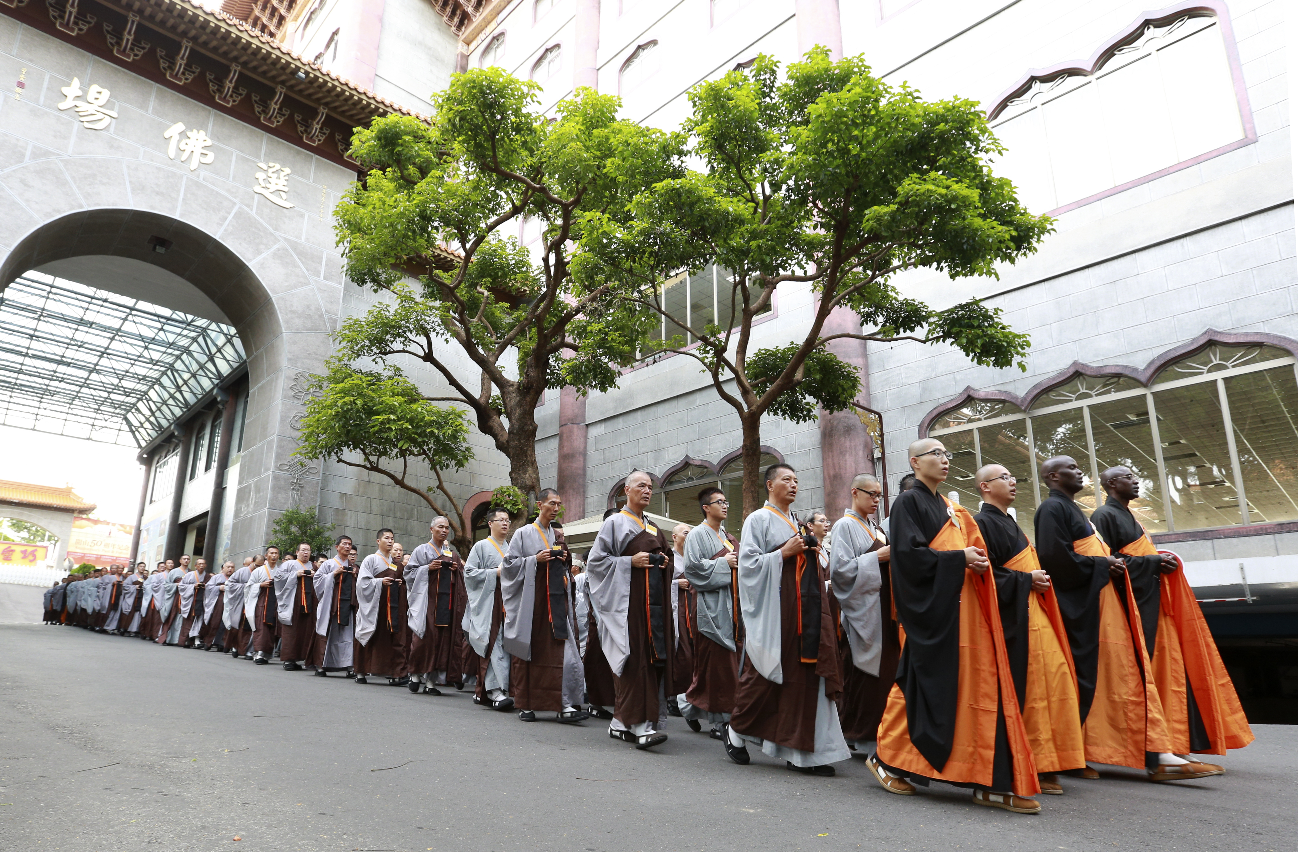Preceptees walk in formation behind their guiding venerables. They are wearing the jiasha robe, holding the sitting mat before them, and carrying the alms bowl in a bag worn over the shoulder. Fo Guang Shan Headquarters, 2016. Photo by Life News Agency.