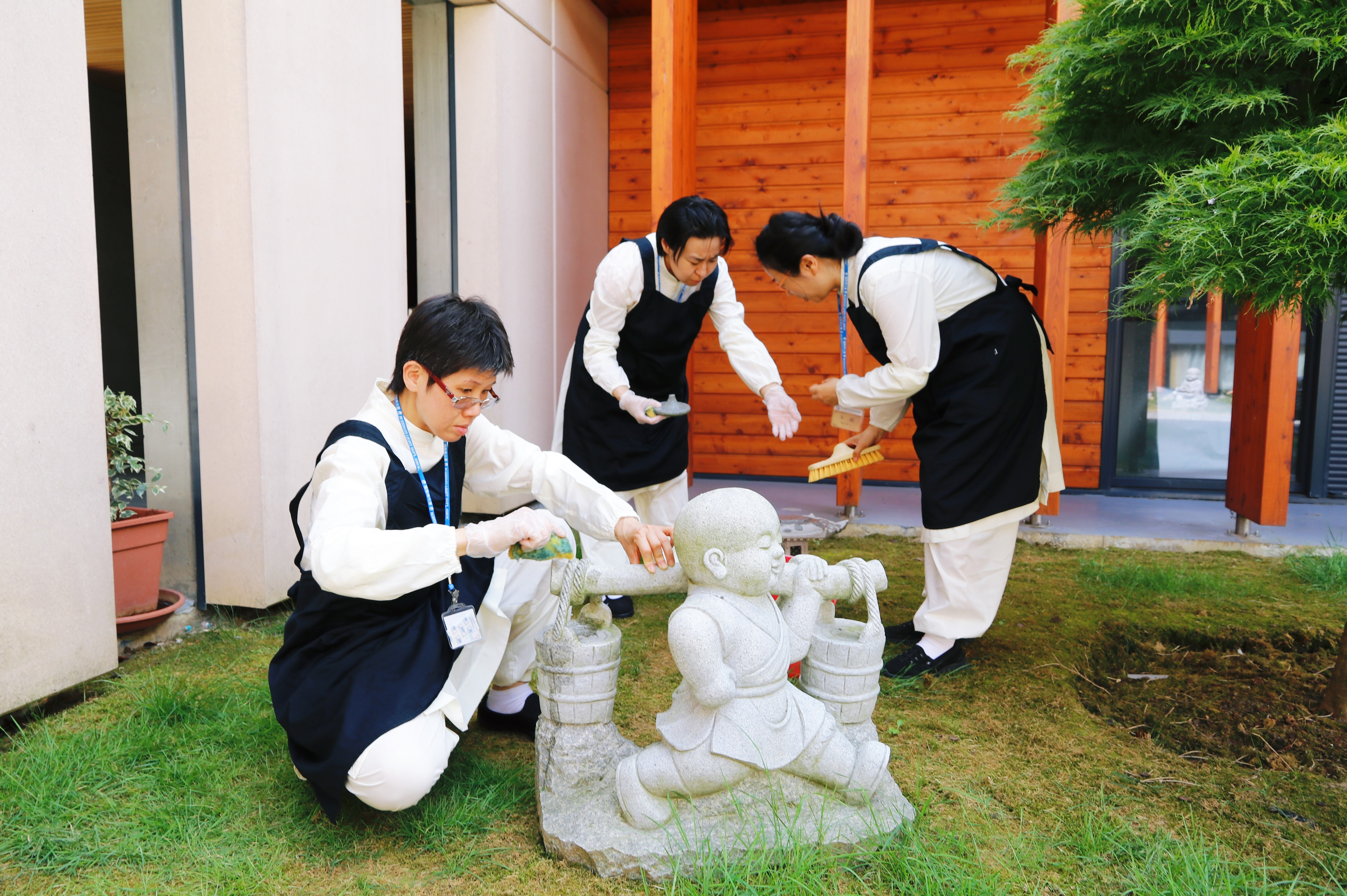 Preceptees carry out chores, carefully cleaning a Buddha statue and other garden ornaments at the Fo Guang Shan European Headquarters, Fahua Temple, Bussy-Saint-Georges, near Paris, 2018. Photo by Life News Agency.