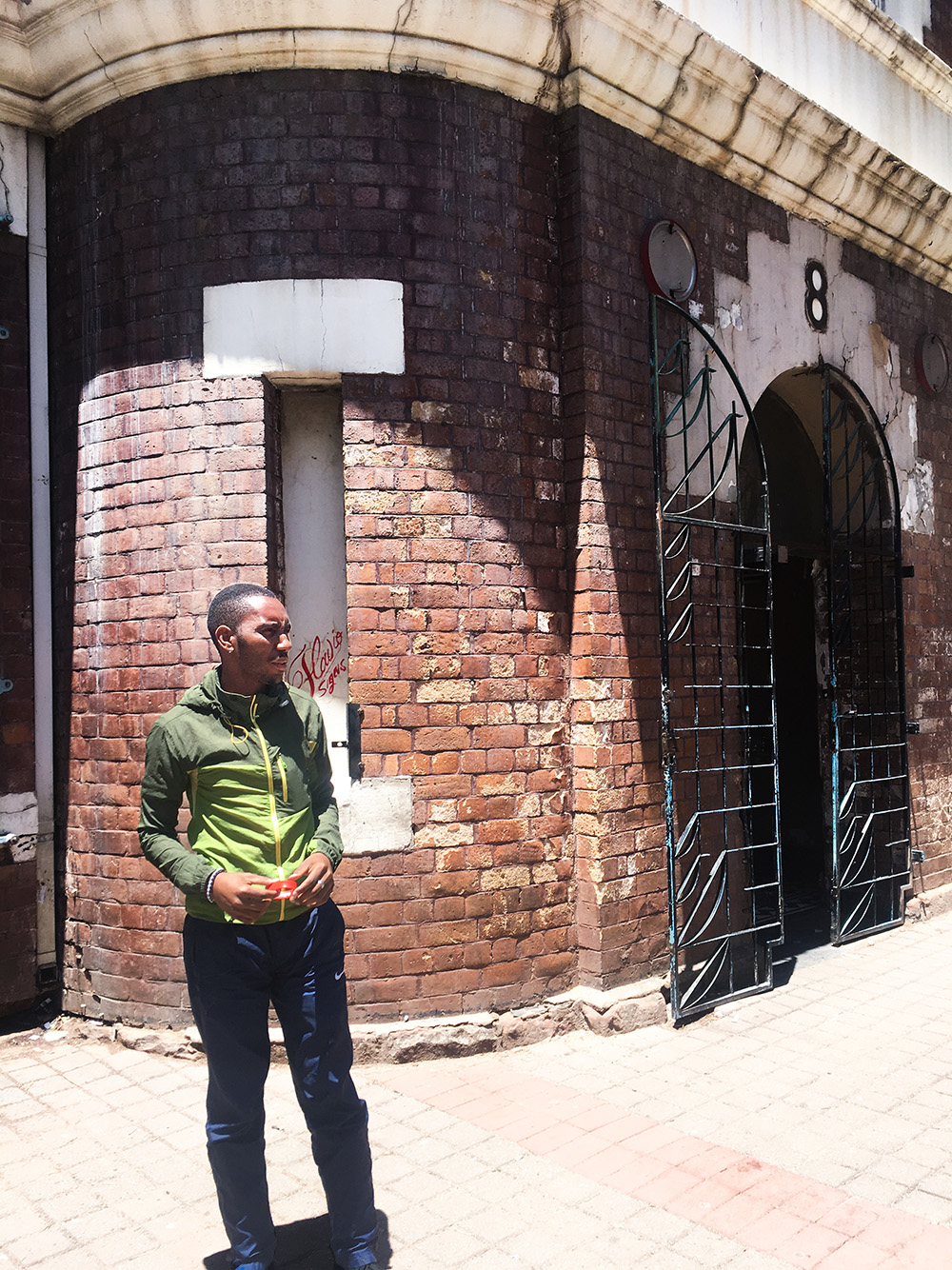 """Siyabonga Mahlangu, General Secretary of the Inner City Federation, outside Ingelosi House—or """"Number 8"""" to residents—in Hillbrow. Photo by Matthew Wilhelm-Solomon, 2017."""