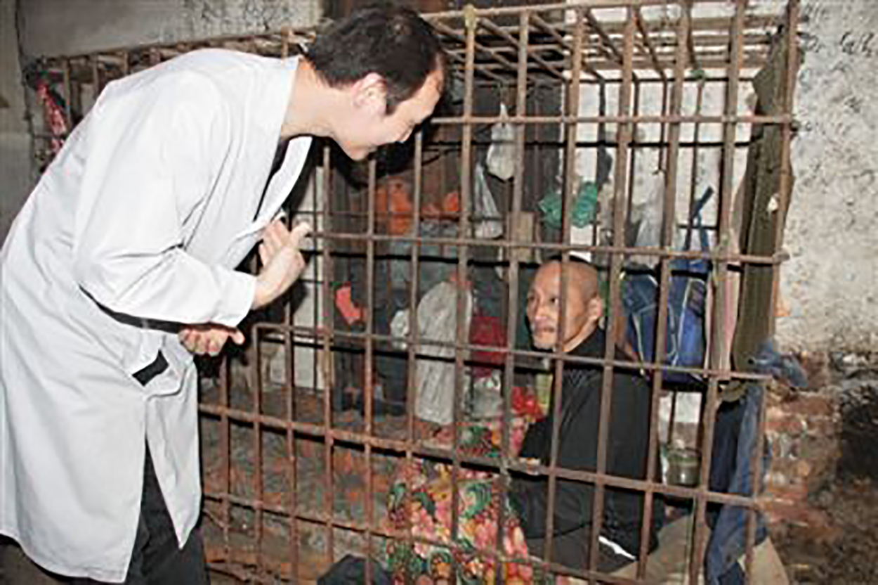 A patient who has lived in a cage for ten years is rescued by hospital psychiatrists. Photo by Beijing News. http://health.sohu.com/20130711/n381262203.shtml.