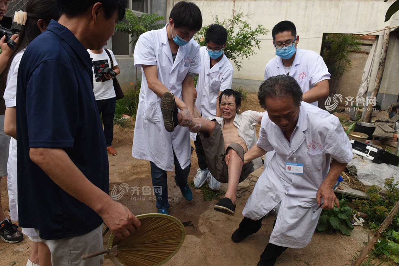 Doctors carry an unchained patient to the hospital while he is kicking and screaming. Photo by Qilu Net. http://yx.iqilu.com/2016/0623/2862679.shtml#10.