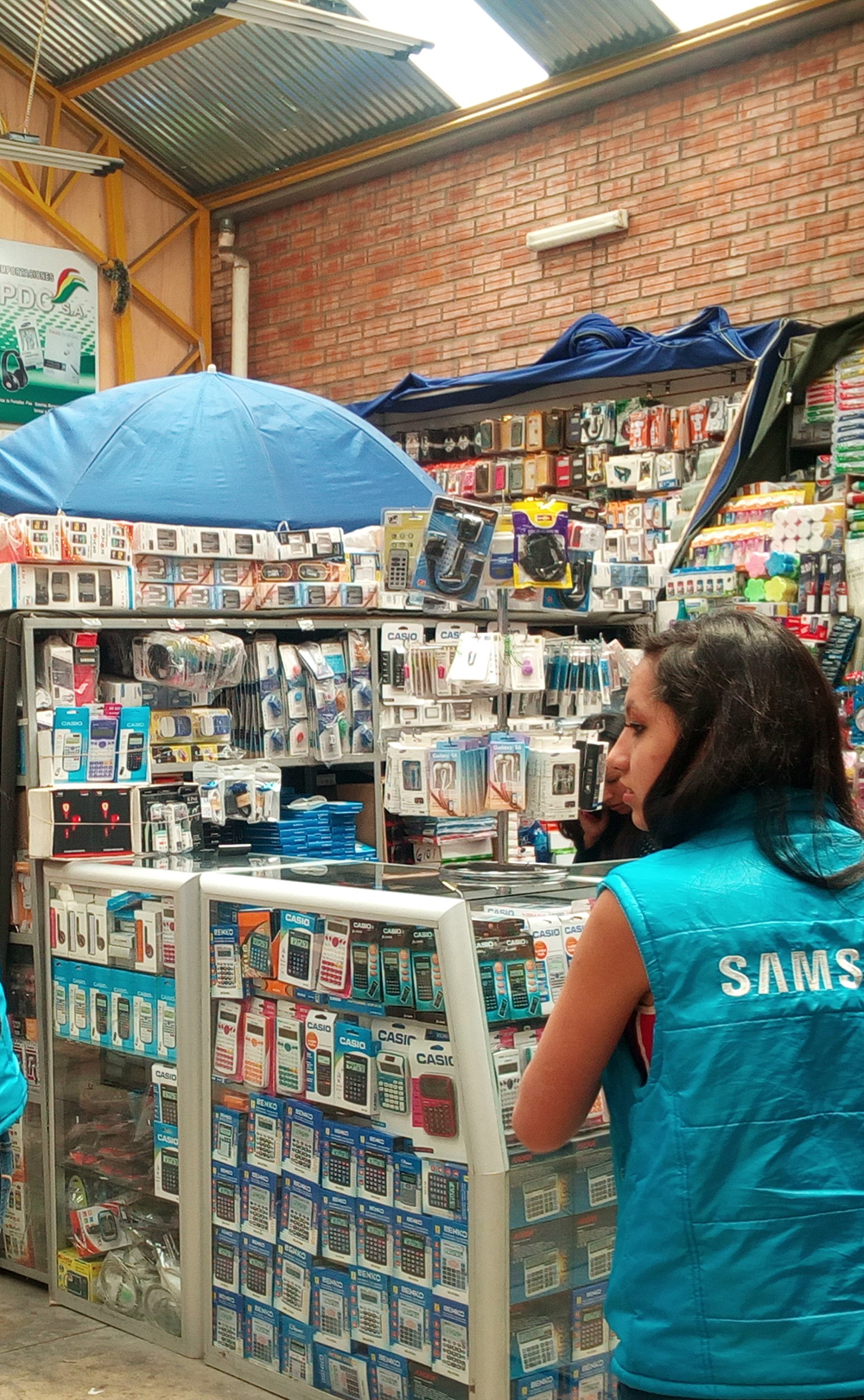 Samsung sales assistant at work in a covered market for mobile phones, gadgets, and small electronic products in La Paz. Photo by Juliane Müller.