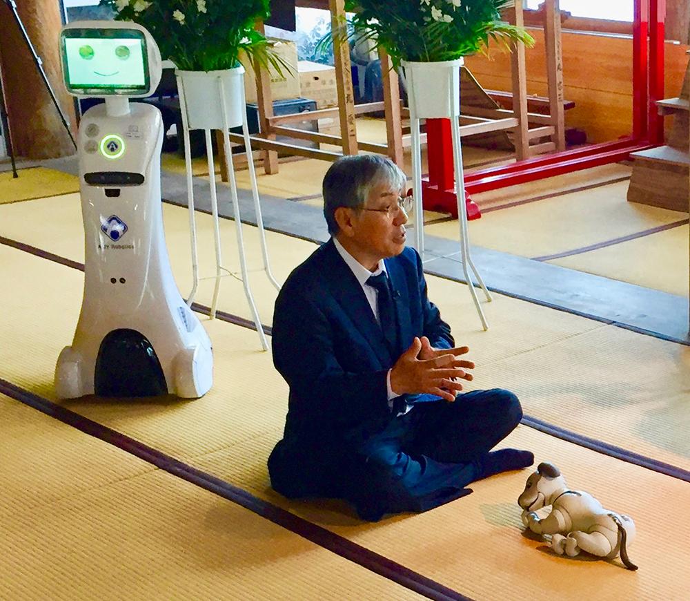 A-FUN Corporation's Norimatsu Nobuyuki with Sony's 2018 aibo and service robot by AMY Robotics. Photo by Daniel White.