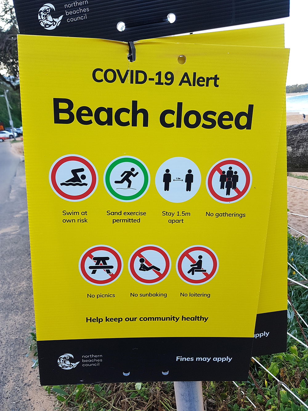 """A sign on a northern Sydney beach announcing that the beach was closed for social and leisure activities such as picnicking and """"sunbaking,"""" but that sand exercise and swimming were permitted. Photo by David Inglis."""
